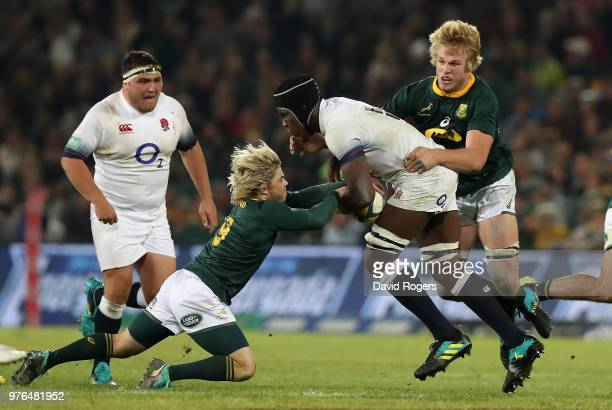 Maro Itoje of England is tackled by Faf de Klerk and PieterSteph du Toit during the second test match between South Africa and England at Toyota...