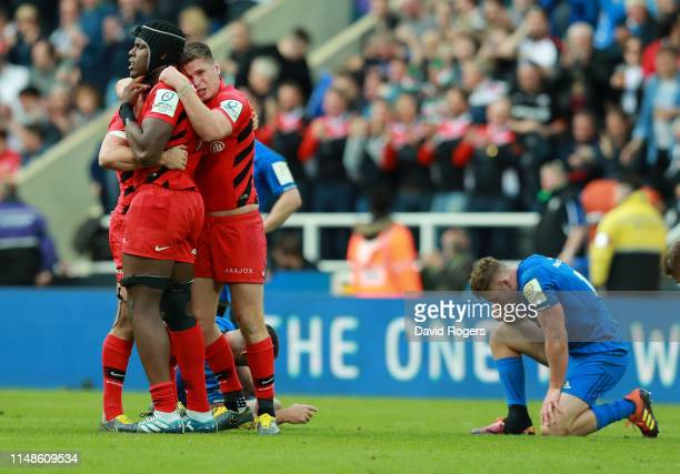 Maro Itoje of Saracens celebrates with team mates Alex Goode and Owen Farrell after their victory during the Champions Cup Final match between...