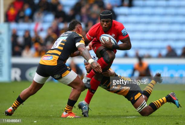 Maro Itoje of Saracens is tackled by Nathan Hughes and Nizaam Carr of Wasps during the Gallagher Premiership Rugby match between Wasps and Saracens...