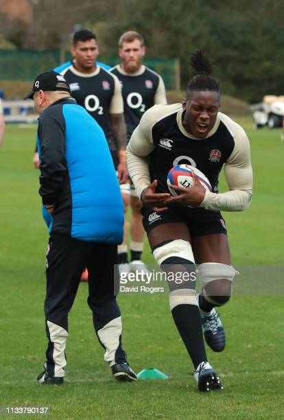 Maro Itoje seems to grimace in pain after falling as he goes past head coach Eddie Jones during the England training session held at Pennyhill Park...