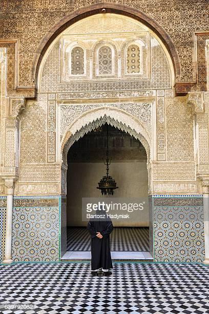 Maroccan man walking inside of Attarin Medersa in Fes, Morocco