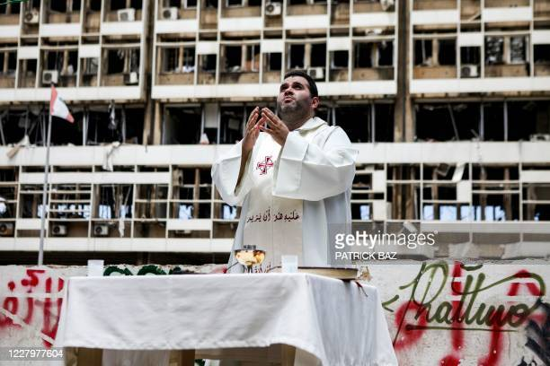 Maronite Christian priest prays as he holds an outdoor Sunday mass before a partially destroyed building in the Mar Mikhael neighbourhood of...