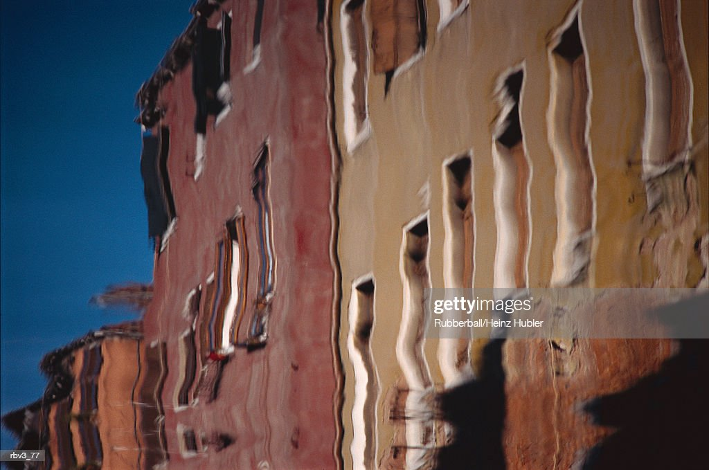maroon and beige buildings with white frames can be seen reflected in canal water : Foto de stock
