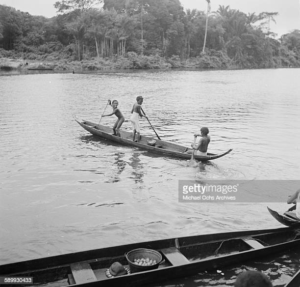 Maroon children paddle a canoe on the river The Maroon Communities are comprised of escaped slaves and indigenous peoples in Suriname
