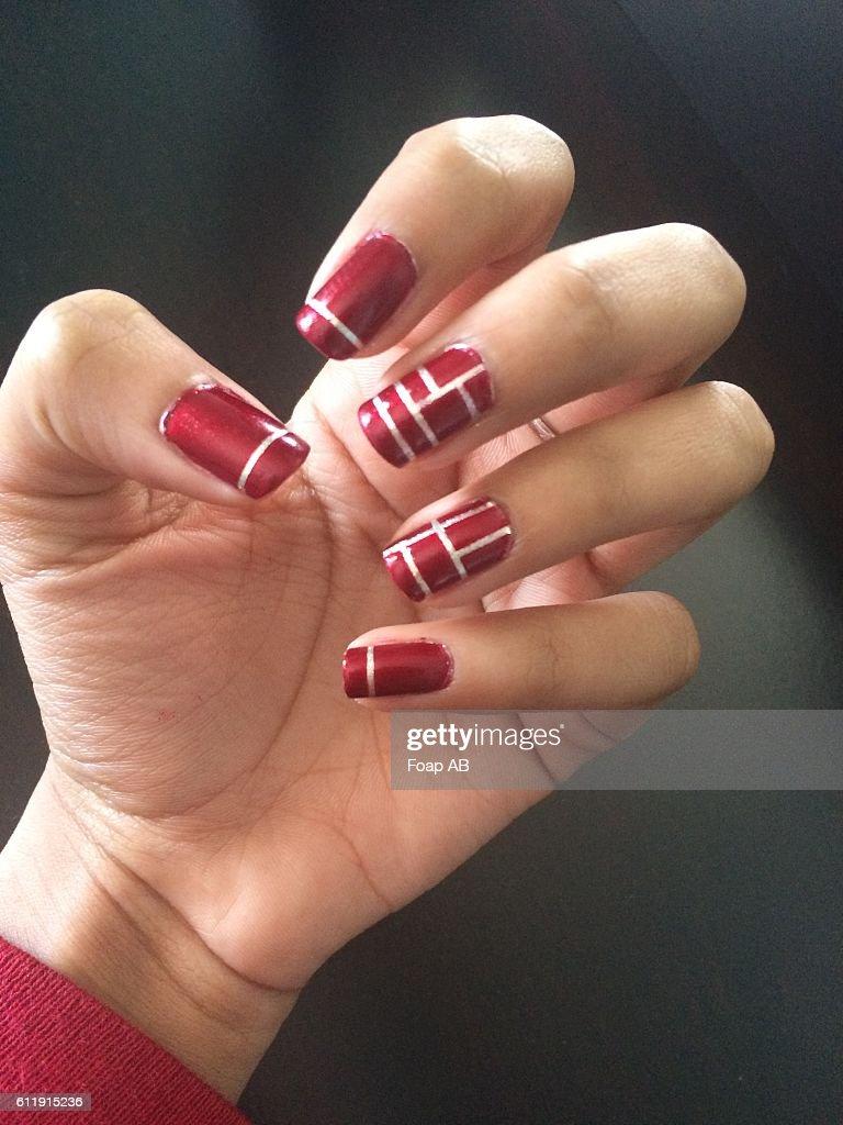 Maroon Nail Polish On Womens Fingernails Stock Photo - Getty Images