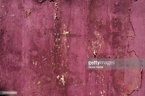 maroon paint peeling off a concrete stucco building exterior wall - bordeauxrood stockfoto's en -beelden