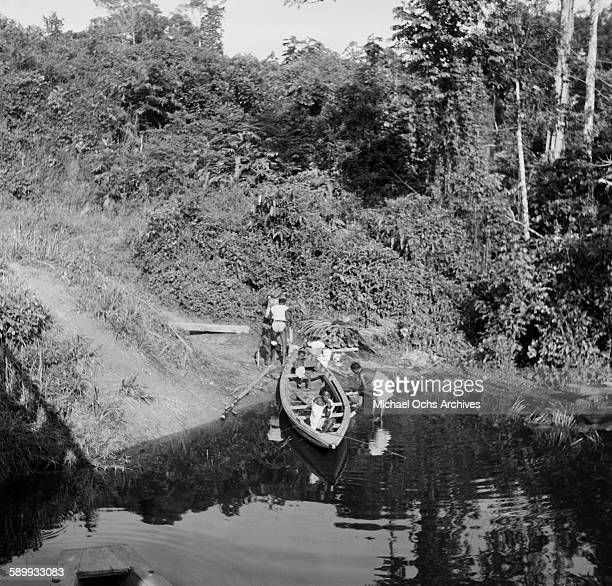 Maroon villagers prepare the canoes on the river The Maroon Communities are comprised of escaped slaves and indigenous peoples in Suriname