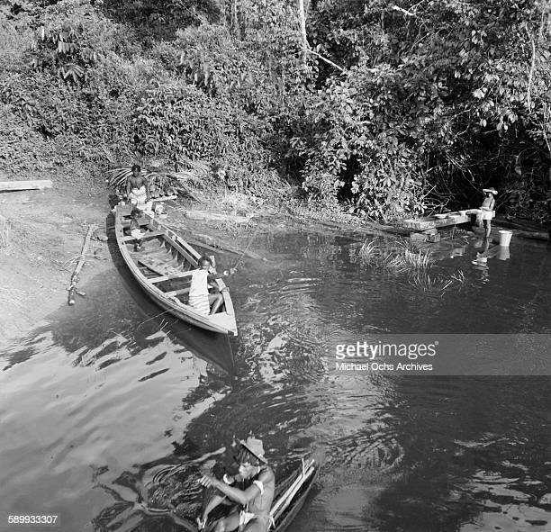 Maroon villages prepare to take a canoe out on the river The Maroon Communities are comprised of escaped slaves and indigenous peoples in Suriname