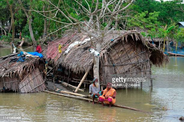 A marooned elderly couple sit on a log close to their home surrounded by high waters in Khulna on May 4 as Cyclone Fani reached Bangladesh Cyclone...