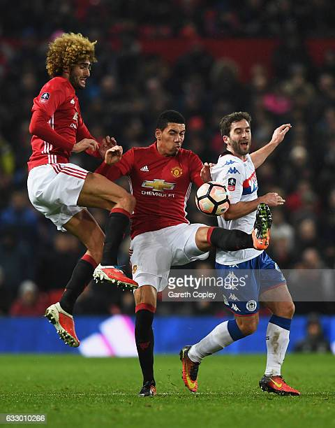 Marouane Fellaini and Chris Smalling of Manchester United battles with Will Grigg of Wigan Athletic during the Emirates FA Cup Fourth round match...