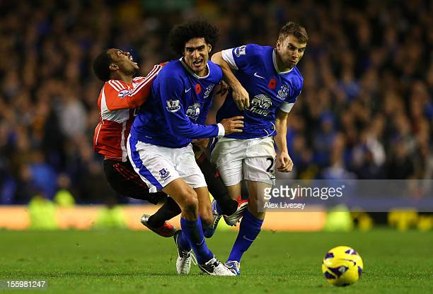Marouane Fellaini and Seamus Coleman of Everton tackle Danny Rose of Sunderland during the Barclays Premier League match between Everton and...