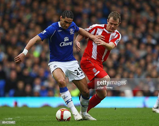 Marouane Fellaini of Everton holds off Glenn Whelan of Stoke during the Barclays Premier League match between Everton and Stoke at Goodison Park on...