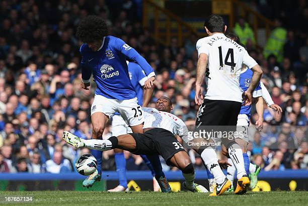 Marouane Fellaini of Everton is tackled by Eyong Enoh of Fulham during the Barclays Premier League match between Everton and Fulham at Goodison Park...