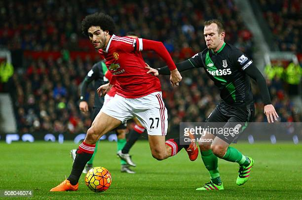 Marouane Fellaini of Manchester United and Glenn Whelan of Stoke City compete for the ball during the Barclays Premier League match between...
