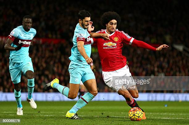 Marouane Fellaini of Manchester United and James Tomkins of West Ham United compete for the ball during the Barclays Premier League match between...