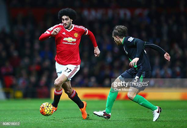 Marouane Fellaini of Manchester United and Marc Muniesa of Stoke City compete for the ball during the Barclays Premier League match between...