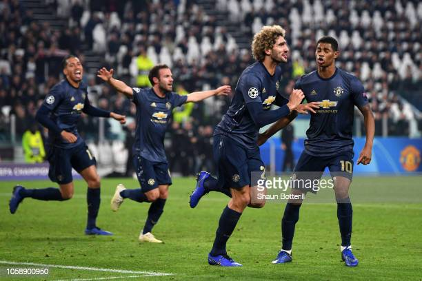 Marouane Fellaini of Manchester United celebrates his sides second goal which came through a Alex Sandro of Juventus own goal with Marcus Rashford of...