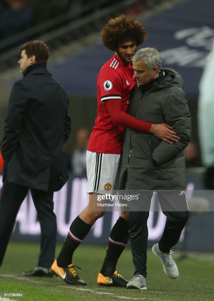 Marouane Fellaini of Manchester United collides with Manager Jose Mourinho after being substituted during the Premier League match between Tottenham Hotspur and Manchester United at Wembley Stadium on January 31, 2018 in London, England.