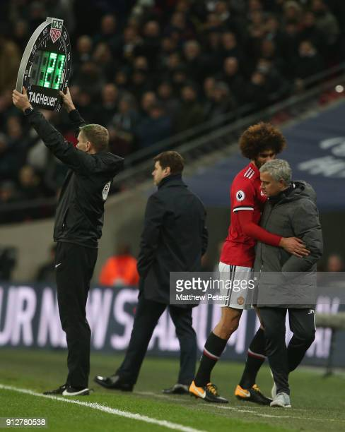 Marouane Fellaini of Manchester United collides with Manager Jose Mourinho after being substituted during the Premier League match between Tottenham...
