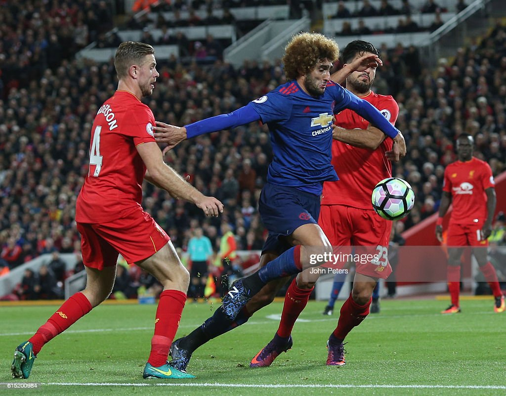 Marouane Fellaini of Manchester United in action with Jordan Henderson and Emre Can of Liverpool during the Premier League match between Liverpool and Manchester United at Anfield on October 17, 2016 in Liverpool, England.