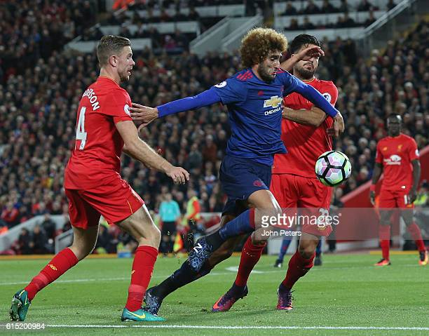 Marouane Fellaini of Manchester United in action with Jordan Henderson and Emre Can of Liverpool during the Premier League match between Liverpool...