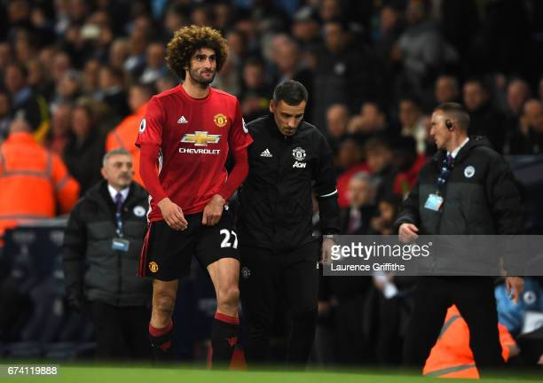Marouane Fellaini of Manchester United is escorted off the pitch after being shown a red card during the Premier League match between Manchester City...