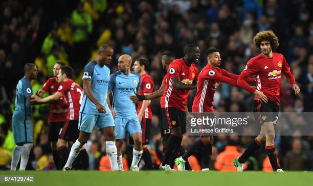 Marouane Fellaini of Manchester United is escorted off the pitch by his team mates after he is shown a red card during the Premier League match...
