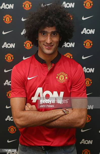 Marouane Fellaini of Manchester United poses in a Manchester United shirt after signing for the club at Aon Training Complex on September 2, 2013 in...