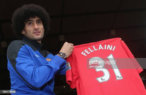 Marouane Fellaini of Manchester United poses with a United shirt after a press conference to announce his signing at Old Trafford on September 13,...