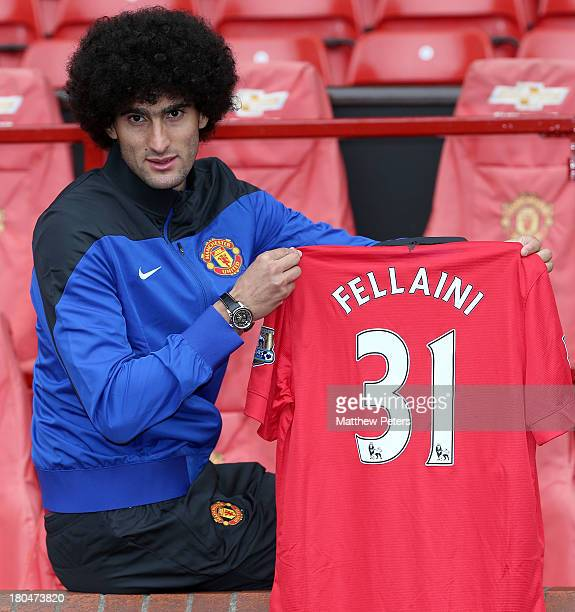 Marouane Fellaini of Manchester United poses with a United shirt after the press conference to announce his signing at Old Trafford on September 13,...