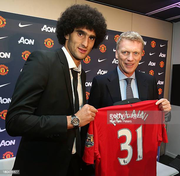 Marouane Fellaini of Manchester United poses with manager David Moyes and a United shirt after the press conference to announce his signing at Old...