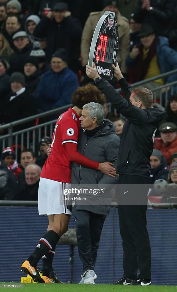 Marouane Fellaini of Manchester United speaks with Manager Jose Mourinho after being substituted during the Premier League match between Tottenham Hotspur and Manchester United at Wembley Stadium on January 31, 2018 in London, England.