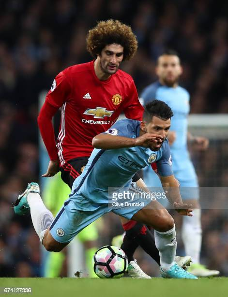 Marouane Fellaini of Manchester United tackles Sergio Aguero of Manchester City in the build up to Marouane Fellaini being shown a red card during...