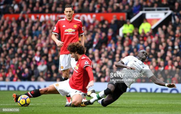 Marouane Fellaini of Manchester United taclkes Sadio Mane of Liverpool inside the box during the Premier League match between Manchester United and...