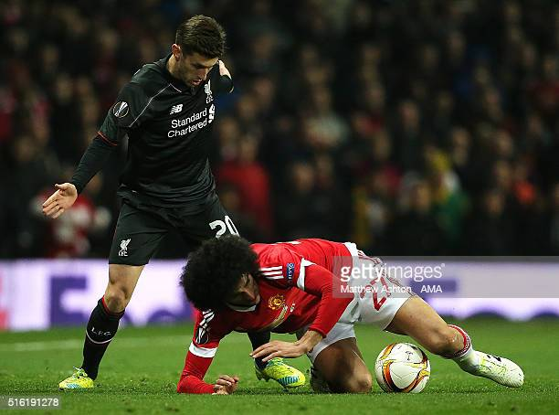 Marouane Fellaini of Manchester United tangles with Adam Lallana of Liverpool during the UEFA Europa League Round of 16 Second Leg match between...
