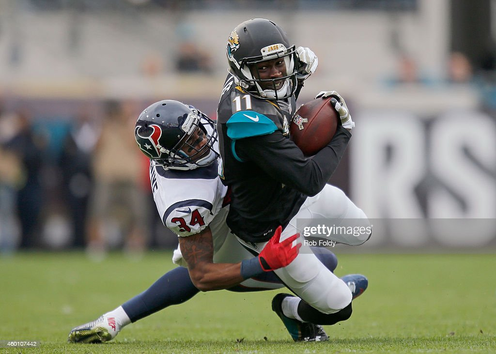 Marqise Lee #11 of the Jacksonville Jaguars carries past A.J. Bouye #34 of the Houston Texans during the first half of the game at EverBank Field on December 7, 2014 in Jacksonville, Florida.