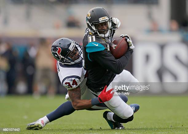Marqise Lee of the Jacksonville Jaguars carries past AJ Bouye of the Houston Texans during the first half of the game at EverBank Field on December 7...