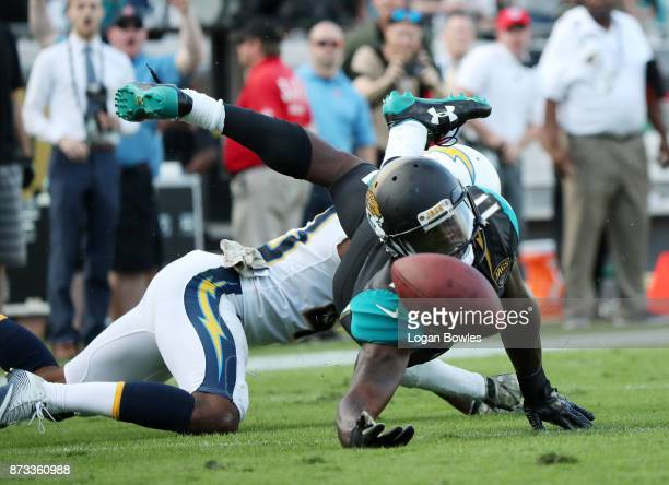 Marqise Lee of the Jacksonville Jaguars reaches for the football in front of Michael Davis of the Los Angeles Chargers in the second half of their...