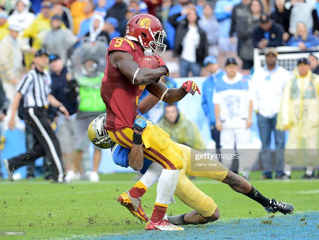 Marqise Lee #9 of the USC Trojans scores a touchdown as he is tackled by Sheldon Price #22 of the UCLA Bruins at Rose Bowl on November 17, 2012 in Pasadena, California. The UCLA Bruins beat the USC Trojans 38-28.