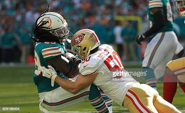 MarQueis Gray of the Miami Dolphins is tackled by Nick Bellore of the San Francisco 49ers during a game on November 27, 2016 in Miami Gardens,...