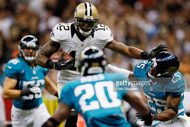 Marques Colston of the New Orleans Saints avoids a tackle by Dwight Lowery of the Jacksonville Jaguars at the MercedesBenz Superdome on August 17...