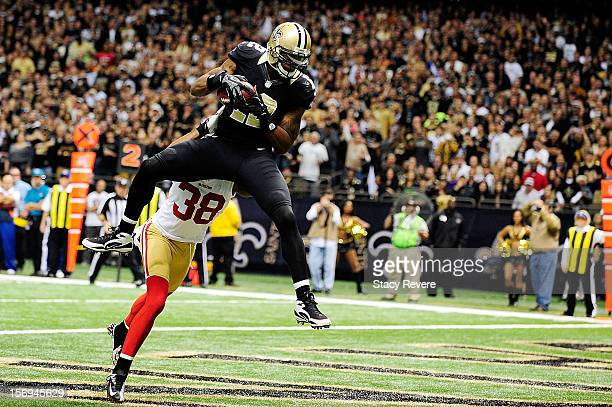 Marques Colston of the New Orleans Saints catches a touchdown pass in front of Dashon Goldson of the San Francisco 49ers during a game at the...