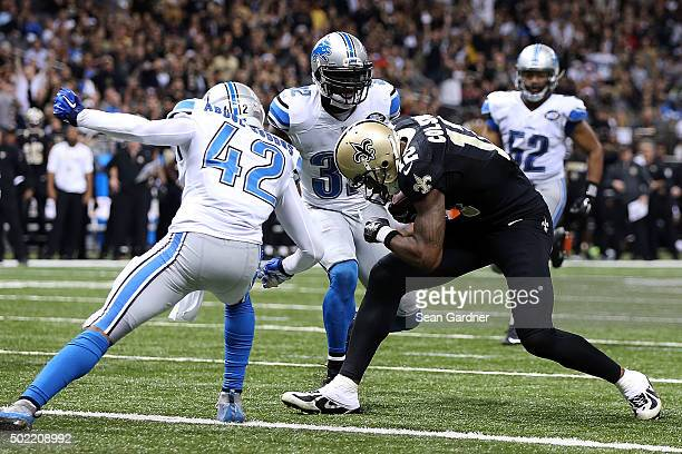 Marques Colston of the New Orleans Saints is hit by Isa AbdulQuddus of the Detroit Lions as he scores a touchdown during the fourth quarter of a game...