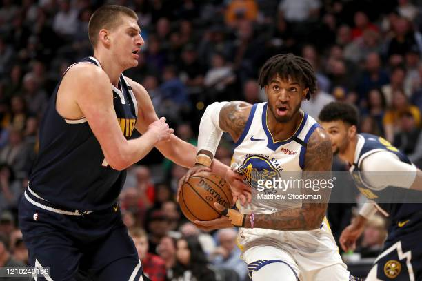 Marquese Chriss of the Golden State Warriors drives against Nikola Jokic of the Denver Nuggets in the first quarter at the Pepsi Center on March 03...