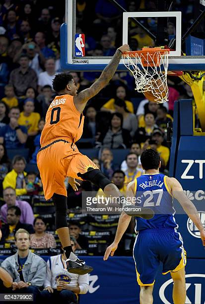 Marquese Chriss of the Phoenix Suns goes up to slam dunk the ball over Zaza Pachulia of the Golden State Warriors during an NBA basketball game at...