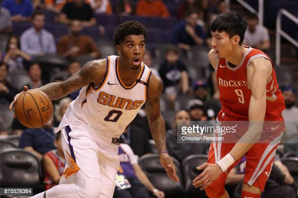 Marquese Chriss of the Phoenix Suns moves the ball past Zhou Qi of the Houston Rockets during the second half of the NBA game at Talking Stick Resort...