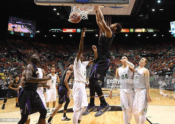 Marquese Chriss of the Washington Huskies dunks against Chris Boucher of the Oregon Ducks during a quarterfinal game of the Pac12 Basketball...