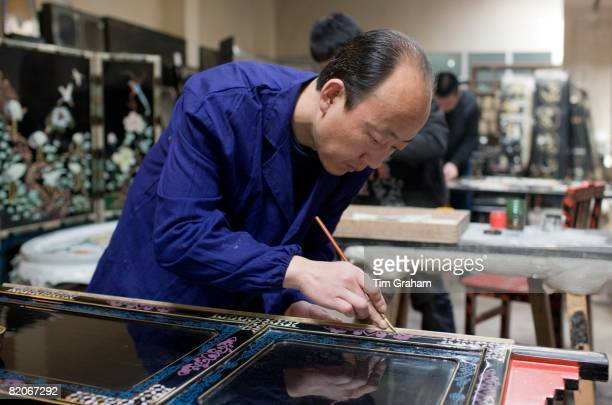 Marquetry craftsman at work on lacquer fire screen at souvenir and furniture factory Xian China