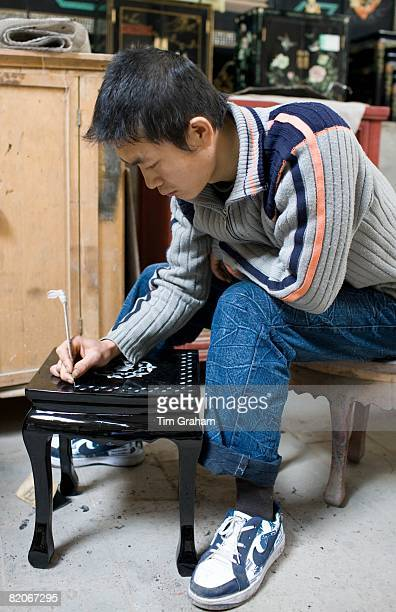 Marquetry craftsman at work on lacquer table at souvenir and furniture factory Xian China