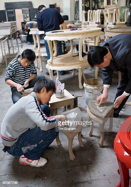 Marquetry craftsmen at work on lacquer tables at souvenir and furniture factory Xian China